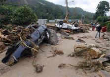 <p>Жители Терезополиса проходят мимо машин, пострадавших от схода оползня, вызванного ливневыми дождями, 13 января 2011 года. Число жертв наводнений и оползней в Бразилии достигло 482 человек, но может увеличиться, поскольку спасатели продолжают поиски погибших. REUTERS/Bruno Domingos</p>