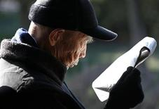 <p>An elderly man reads newspapers on a street in Beijing December 22, 2010. REUTERS/Petar Kujundzic</p>
