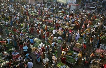 People shop at an open air vegetable and fruit market in the western Indian city of Ahmedabad January 6, 2011. REUTERS/Amit Dave
