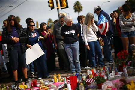 People look at items left by well-wishers outside the office of U.S. Rep. Gabrielle Giffords in Tucson, Arizona January 16, 2011. REUTERS/Eric Thayer