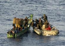 <p>Бойцы НАТО задерживают подозреваемых пиратов в Аденском заливе 26 сентября 2009 года. Число нападений пиратов на морские суда достигло в 2010 году пика последних семи лет, а количество взятых в плен заложников стало рекордным, несмотря на усиленное патрулирование, сообщило во вторник Международное морское бюро (IMB). REUTERS/Turkish Chief of Staff/Handout</p>