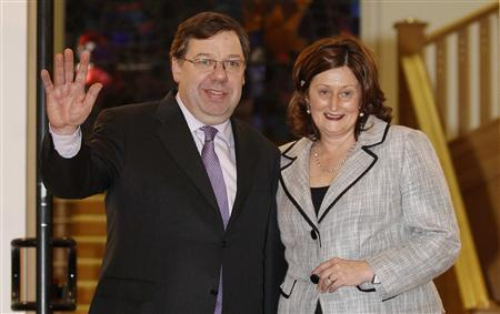 Brian Cowen, Irish Prime Minister and leader of Fianna Fail, waves to photographers with his wife Mary after winning a vote of confidence from members of his own party in Dublin January 18, 2011. REUTERS/Cathal McNaughton