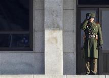 <p>Северокорейский солдат смотрит на юг в сторону демилитаризованной зоны, разделяющей две Кореи, 19 января 2011 года. США предупредили Китай, что вернут войска в Азию, если Пекин не сможет утихомирить союзную ему Северную Корею, сообщила газета New York Times в пятницу. REUTERS/Lee Jae-Won</p>