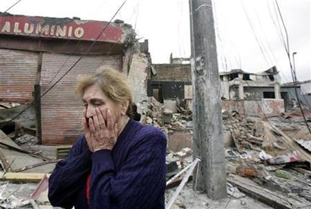 An earthquake survivor walks through the city center after it was destroyed by a massive earthquake and ensuing tsunami, in Talcahuano March 4, 2010. REUTERS/Mariana Bazo