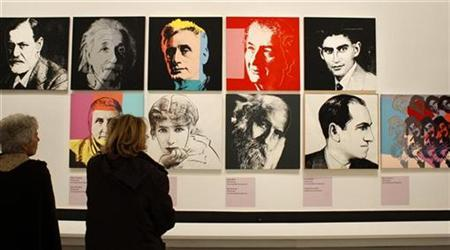 Visitors look at paintings by U.S. artist Andy Warhol during the exhibition ''Le grand Monde d'Andy Warhol'' (The World of Andy Warhol) at the Grand Palais museum in Paris March 17, 2009. REUTERS/Benoit Tessier