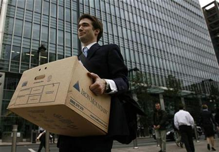 A worker carries a box out of the U.S. investment bank Lehman Brothers offices in the Canary Wharf district of London in this September 15, 2008 file photo. The Bank of England estimates governments the world over have spent or committed a staggering $14 trillion to prop up the financial system following the fall of Lehman Brothers in September 2008. Despite the protestations by politicians that such a large-scale rescue should never be allowed to happen again, their actions over the past two years suggest the opposite. Picture taken September 15, 2008. REUTERS/Andrew Winning