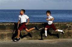 <p>Кубинские школьники бегут по набережной в Гаване, 28 октября 2010 года. На социалистической Кубе, где большинству людей никогда не приходилось платить налоги, разрабатывают видеоигру, которая поможет школьникам понять важность уплаты денег в государственную казну. REUTERS/Enrique De La Osa</p>