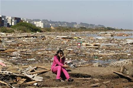 A girl sits among the debris left by a major earthquake and ensuing tsunami in Llolleo, March 3, 2010. REUTERS/Eliseo Fernandez