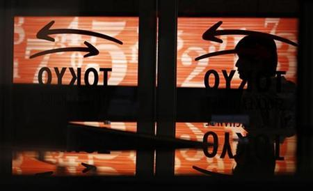 A man walks past a glass wall with logos of the Tokyo Stock Exchange at the bourse in Tokyo November 4, 2010. REUTERS/Yuriko Nakao