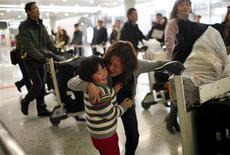 <p>Женщина, прилетевшая из Египта, обнимает ребенка в аэропорту в Шанхае, 31 января 2011 года. Правительства, авиалинии и туроператоры совместно взялись за эвакуацию иностранцев из Египта, охваченного многодневными массовыми акциями протеста против президента Хосни Мубарака. REUTERS/Carlos Barria</p>
