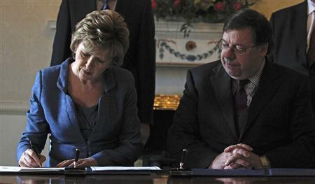 Irish Prime Minister Brian Cowen watches as President Mary McAleese signs the proclamation of dissolution of the Irish parliament, at her official residence in Dublin, February 1, 2011. REUTERS/Cathal McNaughton