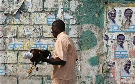 A Haitian man carries a fighting cock while he walks next to poster of Haiti's presidential candidate Jude Celestin in Port-au-Prince January 9, 2011. REUTERS/Eduardo Munoz