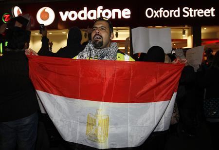 A demonstrator holds an Egyptian flag and yells slogans during a protest outside a Vodafone store in London, February 3, 2011. REUTERS/Andrew Winning