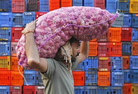 A man carries onions at a wholesale market in Mumbai, January 25, 2011. REUTERS/Danish Siddiqui