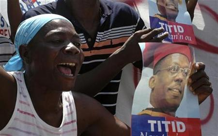 A resident shouts slogans and holds a poster of ousted President Jean Bertrand Aristide while taking part in a protest in Port-au-Prince May 10, 2010. REUTERS/ St-Felix Evens