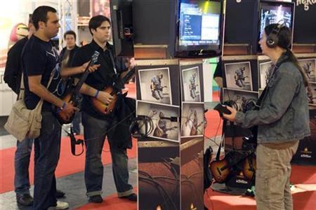 Visitors play Guitar Hero 5 game during the video game show in Paris September 17, 2009. REUTERS/Charles Platiau