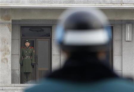 A North Korean soldier looks south, as a South Korean soldier (front) stands guard, at the truce village of Panmunjom in the demilitarised zone separating the two Koreas in Paju, about 55 km (34 miles) north of Seoul, December 8, 2010. REUTERS/Jo Yong-Hak