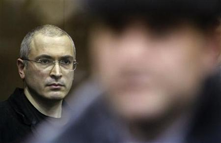Jailed Russian former oil tycoon Mikhail Khodorkovsky (L) stands in the defendants' cage during a court session in Moscow December 30, 2010. REUTERS/Denis Sinyakov