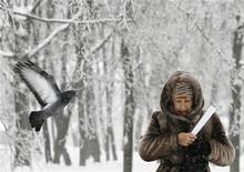 <p>Голубь пролетает мимо женщины на улице в Москве, 29 декабря 2010 года. После очень холодной рабочей недели морозная и ясная погода сохранится в Москве и в выходные, ожидают синоптики. REUTERS/Denis Sinyakov</p>