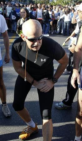 Greece's Prime Minister George Papandreou stretches before taking part in a 10K race in Athens October 31, 2010. REUTERS/Yiorgos Karahalis (GREECE - Tags: SPORT ATHLETICS POLITICS)