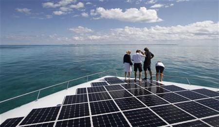 People stand on the world's largest solar-powered boat in Cancun December 8, 2010. REUTERS/Gerardo Garcia