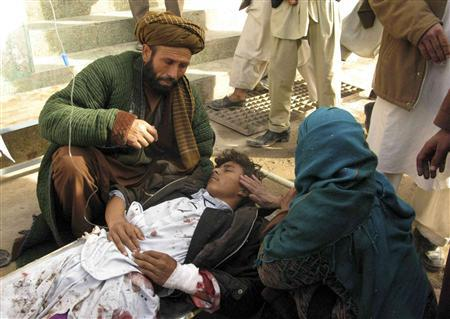 A mother touches her wounded son after a suicide attack in Emam Saheb district of Kunduz province February 21, 2011. REUTERS/Wahdat
