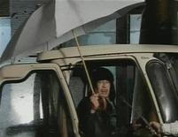 <p>Кадр из телеобращения Муаммара Каддафи к жителям Ливии, 22 февраля 2011 года. Лидер Ливии Муаммар Каддафи продемонстрировал свою готовность решительно бороться с усиливающимися народными выступлениями, участники которых стремятся положить конец его 41-летнему правлению в богатой нефтью североафриканской стране. REUTERS/Libya TV via Reuters TV</p>