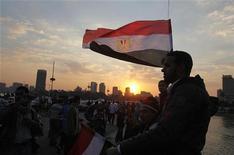 """<p>Участник антиправительственной демонстрации в Каире держит египетский флаг, 12 февраля 2011 года. Сторонники демократии призвали жителей Египта выйти на массовые демонстрации и потребовать отставки временного правительства, где слишком много """"знакомых лиц"""". REUTERS/Asmaa Waguih</p>"""