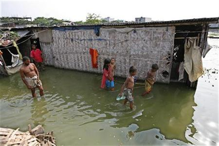 People wade through stagnant water in the outskirts of Dhaka August 4, 2009. REUTERS/Andrew Biraj
