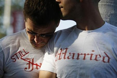 Gay couple Ethan Collings (L), 32, and his spouse Stephen Abate, 36, hug as they celebrate their one-year wedding anniversary in West Hollywood, California, June 16, 2009. The couple were married when same-sex marriages were first allowed in 2008. REUTERS/Lucy Nicholson