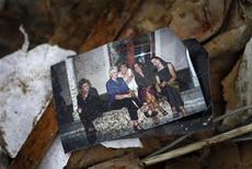 <p>Фотография лежит на обломках дома, обрушившегося в результате землетрясения в Новой Зеландии, 25 февраля 2011 года. Число жертв землетрясения в Новой Зеландии достигло 113 человек, и по-прежнему более 200 человек числятся пропавшими без вести. REUTERS/Tim Wimborne</p>