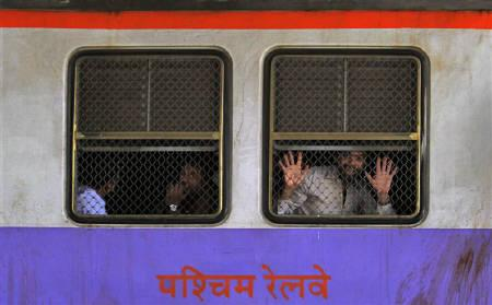 A commuter reacts to the camera in a suburban train during the morning rush hour in Mumbai February 25, 2011. REUTERS/Danish Siddiqui