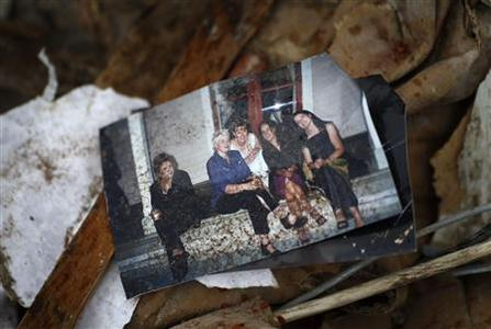 A photograph lies in the remains of a house, which was destroyed by Tuesday's earthquake, in Christchurch February 25, 2011. REUTERS/Tim Wimborne
