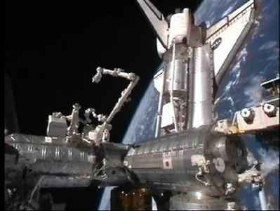 The Space Shuttle Discovery is seen docked with the International Space Station with the earth in the background in this image from NASA TV February 26, 2011. REUTERS/NASA TV