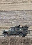 """<p>Военный грузовик везет южно-корейских солдат на севере Сеула, 28 февраля 2011 года. Южная Корея и США начали совместные военные учения на Корейском полуострове, что вызвало волну негатива со стороны Северной Кореи, вновь угрожающей прибегнуть к ядерному оружию и превратить Сеул в """"море огня"""". REUTERS/Jo Yong-Hak</p>"""