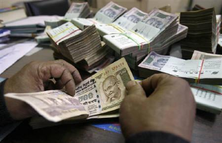 An employee counts rupee notes at a cash counter inside a bank in Agartala, in this December 31, 2010 file photo. REUTERS/Jayanta Dey/Files