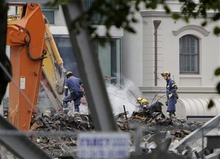 Relief workers sift through the rubble of the CTV building in central Christchurch following Tuesday's earthquake February 26, 2011.REUTERS/Mark Baker/Pool