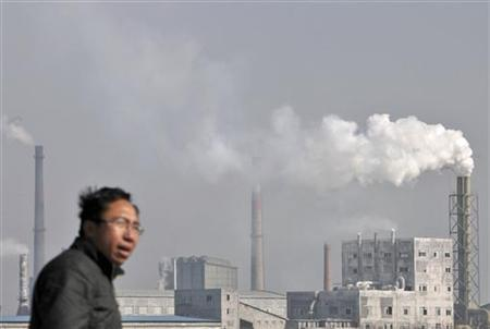 A resident walks in front of chimneys billowing smoke near a chemical plant in Yingtan, Jiangxi province December 9, 2010. REUTERS/Stringer