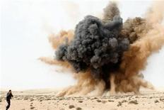 <p>Мужчина бежит, закрыв уши, мимо взорвавшейся бомбы в пустыне близ города Марса-эль-Брега, 2 марта 2011 года. Армия ливийского лидера Муаммара Каддафи сталкивается со все более организованным и уверенным сопротивлением сил мятежников, которые просят международное сообщество оказать им поддержку и намерены закрепить военные успехи на западе страны. REUTERS/Joel Silva/Folhapress</p>