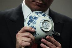 "<p>Sotheby's Asia Deputy Chairman Nicolas Chow poses with a ""Blue and White Palace Bowl with Melons"" at a preview by auction house Sotheby's in Hong Kong in this February 25, 2011 file photo. REUTERS/Tyrone Siu/Files</p>"