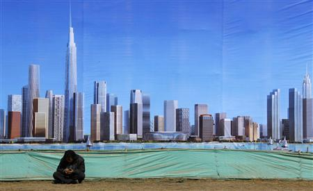 A worker rests in front of a billboard displaying an artist's impression of the new business district of Binhai, located in the Yujiapu financial zone on the outskirts of the city of Tianjin, March 2, 2011. REUTERS/David Gray