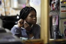 <p>Esther Aikpehae, a 12-year-old born in South Africa, fixes her earring at a beauty salon in south Tel Aviv March 3, 2011. REUTERS/Nir Elias</p>