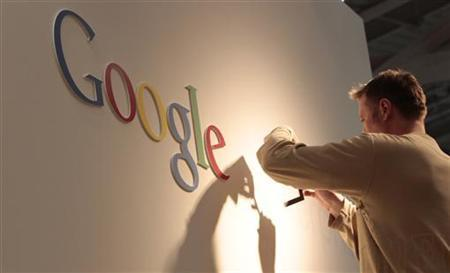 A man works on Google logo at an exhibition stand at the CeBIT computer fair in Hanover, February 28, 2011. REUTERS/Tobias Schwarz
