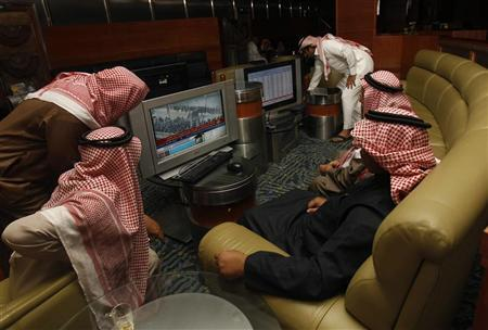 Traders watch a television news report on the situation in Egypt at the Saudi Investment Bank in Riyadh January 31, 2011. REUTERS/Fahad Shadeed (SAUDI ARABIA - Tags: BUSINESS)