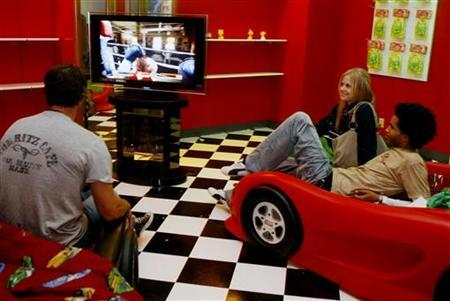 Guests sit on automobile shaped beds as they play a game on the Sony Playstation 3 at a party held by Sony Computer Entertainment America celebrating the new Playstation 3 game console in Beverly Hills November 8, 2006. REUTERS/Fred Prouser