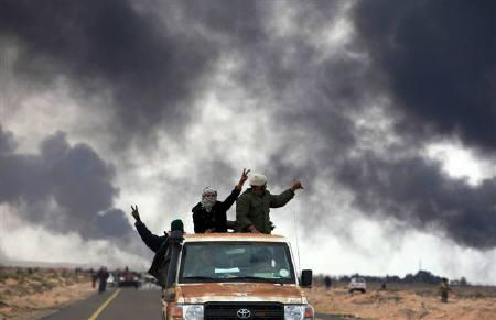 Rebels cheer after a bomb was detonated during clashes with pro-Gaddafi forces between Ras Lanuf and Bin Jawad March 9, 2011. REUTERS/Asmaa Waguih