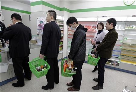 People queue to pay for goods in a store in Tokyo that has almost sold out of food and drink as people are unable to return home after an earthquake March 11, 2011. REUTERS/Yuriko Nakao
