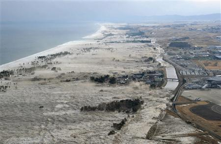 A massive tsunami hits the coastal areas of Iwanuma, Miyagi Prefecture, northeastern Japan, March 11, 2011. REUTERS/KYODO