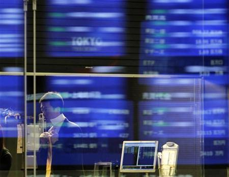 Market prices are reflected in a glass window as a man wears a tie at the Tokyo Stock Exchange March 10, 2011. REUTERS/Toru Hanai