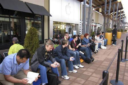 People look at their phones and computers as they wait for the iPad 2 to go on sale at the Apple store in Boulder, Colorado March 11, 2011.  REUTERS/Rick Wilking